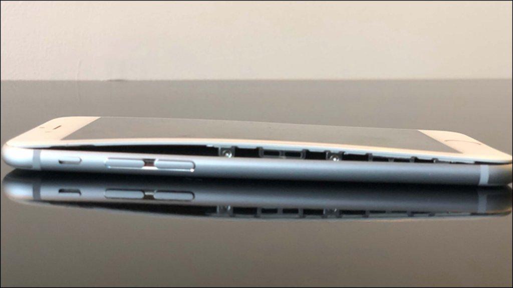 iPhone。膨張したバッテリーがパネルを持ち上げている。